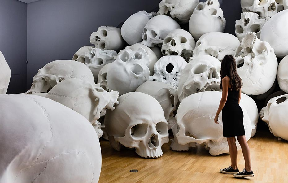 Image of a woman standing in front of an art instillation featuring giant skulls